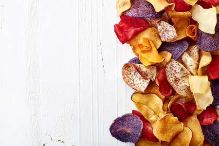 Heap of healthy colorful vegetable chips on white wooden background from top view Stock Photo