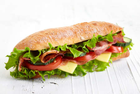 Fresh submarine sandwich with ham, cheese, bacon, tomatoes, cucumbers, lettuce and onions on white wooden background