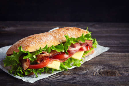 Fresh submarine sandwich with ham, cheese, bacon, tomatoes, cucumbers, lettuce and onions on dark wooden background