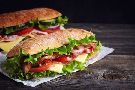 Two fresh submarine sandwiches with ham, cheese, bacon, tomatoes, lettuce, cucumbers and onions on dark wooden background Zdjęcie Seryjne - 64088031