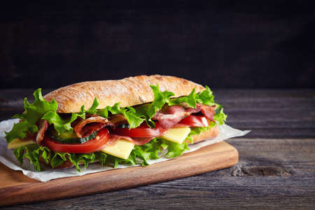 Fresh submarine sandwich with ham, cheese, bacon, tomatoes, cucumbers, lettuce and onions on wooden cutting board
