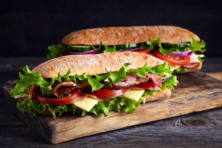 Two fresh submarine sandwiches with ham, cheese, bacon, tomatoes, lettuce, cucumbers and onions on wooden cutting board