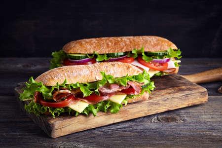 Dos sandwiches frescos submarino con jamón, queso, bacon, tomate, lechuga, pepinos y cebollas en la tabla de cortar madera Foto de archivo
