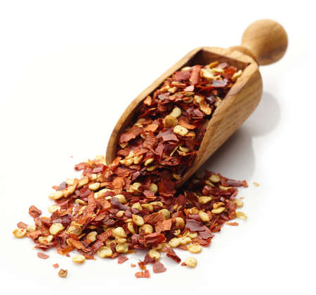 pepper flakes: Wooden scoop of red hot chili pepper flakes isolated on white background Stock Photo