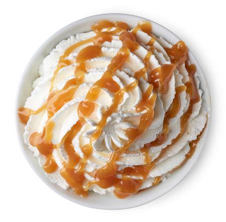 상위 뷰에서 흰색 배경에 고립 된 휘 핑된 크림 및 카라멜 소스 그릇 스톡 콘텐츠