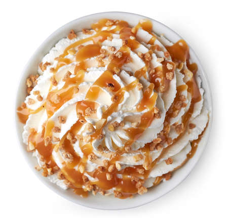 Bowl of whipped cream decorated with caramel sauce and nuts. Isolated on white background. From top view