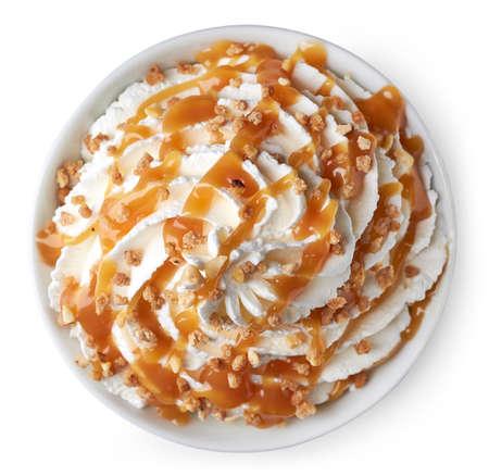 Bowl van slagroom versierd met karamelsaus en noten. Geïsoleerd op een witte achtergrond. Vanaf bovenaanzicht Stockfoto - 66010795