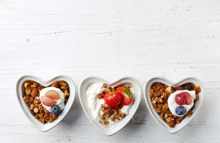 Heart shaped bowls of homemade granola and yogurt on white wooden background from top view
