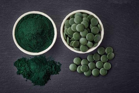 spirulina: Bowls of spirulina algae powder and tablets on black background Stock Photo
