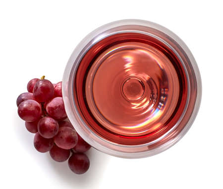 Glass of rose wine and grapes isolated on white background from top view Stockfoto