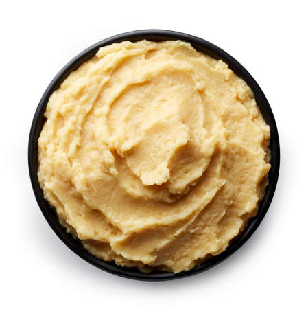 Black bowl of homemade hummus isolated on white background from top view