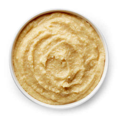 Bowl of homemade hummus isolated on white background from top view