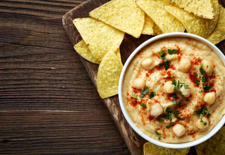 humus: Bowl of homemade hummus and nachos on brown wooden background from top view Stock Photo