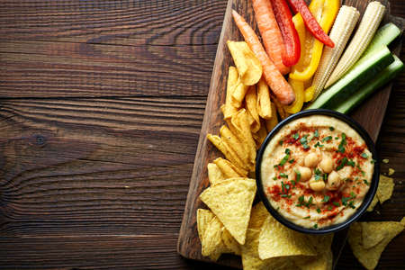 humus: Homemade hummus, nachos and fresh vegetables on wooden background from top view Stock Photo