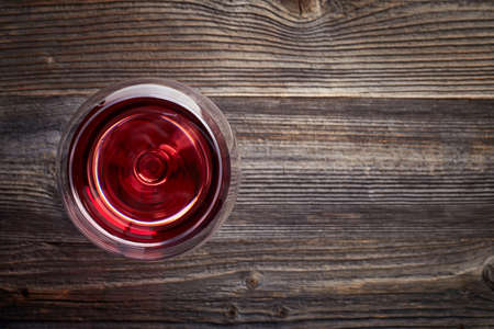 Glass of red wine on dark wooden background from top view