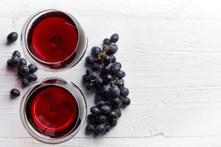 sulphide: Two glasses of red wine and grapes on white wooden background from top view Stock Photo
