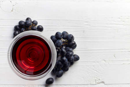 Glass of red wine and grapes on white wooden background from top view