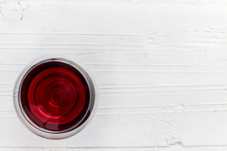 sulphide: Glass of red wine on white wooden background from top view