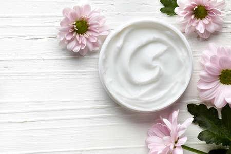 Kosmetische roomcontainer en roze bloemen op witte houten achtergrond van hoogste mening