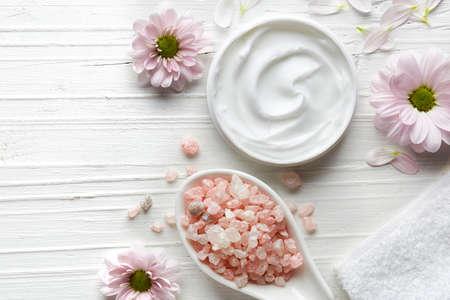contenant de crème cosmétique, sel de bain et de fleurs roses sur fond blanc en bois en vue de dessus Banque d'images