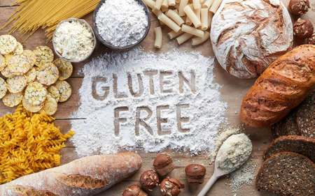 Gluten free food. Various pasta, bread, snacks and flour on wooden background from top view Stock Photo