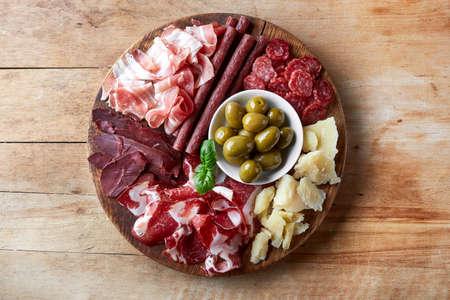 生ハム、サラミ、ベーコン、チーズ、オリーブの木製の背景を持つ燻製ハムのプレート。上から見るから
