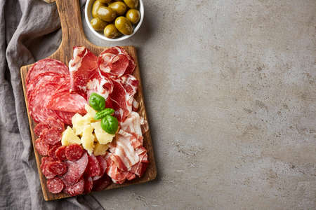 Wooden cutting board with prosciutto, salami and cheese on gray stone background. From top view