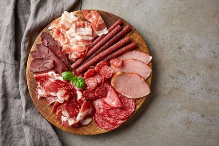 Cold smoked meat plate with prosciutto, salami, bacon, pork chops, cheese and olives on gray stone background. From top view 免版税图像
