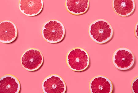 Colorful fruit pattern of fresh grapefruit slices on pink background. From top view Фото со стока