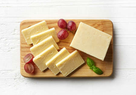 Cutting board of white cheddar cheese on white wooden background. From top view Imagens