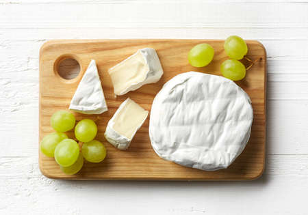Cutting board of camembert cheese and grapes on white wooden background. From top view Stock Photo