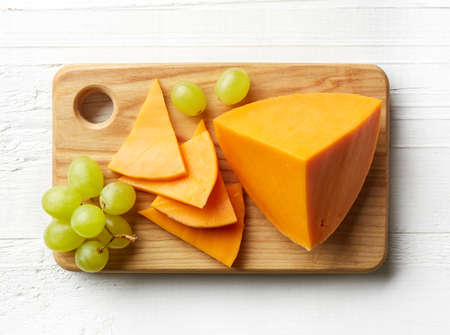 Piece and slices of cheddar cheese on cutting board. From top view
