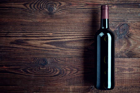 Bottle of red wine on dark wooden background from top view Stock Photo