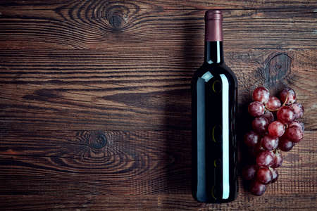 Bottle of red wine and grapes on dark wooden background from top view