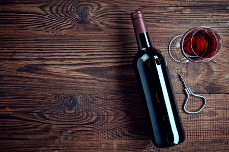 Bottle and glass of red wine on wooden background from top view Stock Photo
