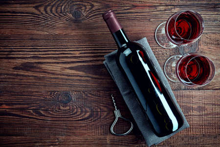 Bottle and two glasses of red wine on wooden background from top view