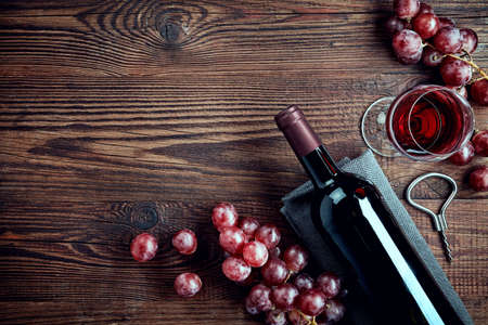 Bottle and glass of red wine and grapes on wooden background from top view