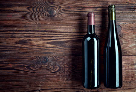 Bottles of red and white wine on wooden background from top view Stock Photo