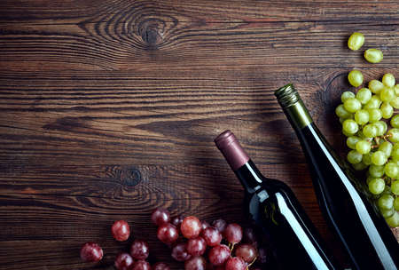 Bottles of red and white wine and grapes on wooden background from top view