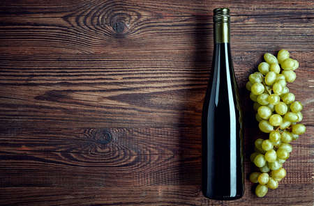 sulphide: Bottle of white wine and grapes on wooden background from top view Stock Photo