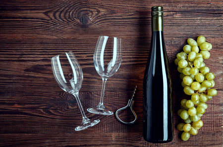 Bottle of white wine, two glasses and grapes on wooden background from top view Stock Photo