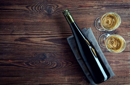 Bottle and two glasses of white wine on wooden background from top view