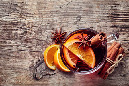Hot mulled wine with spices on old wooden background. Top view