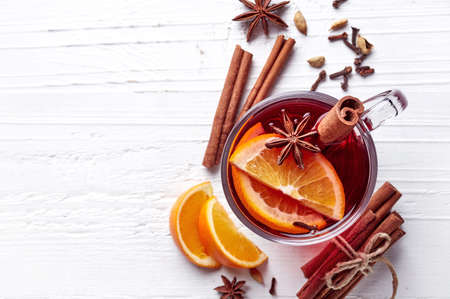 Hot mulled wine with spices on white wooden background. Top view