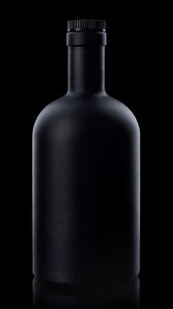 Black whiskey bottle on dark background Imagens