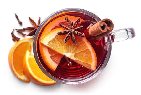 Glass of hot mulled wine with spices isolated on white background. Top view