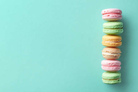 Row of colorful french macarons on blue background. Top view. Pastel colors 스톡 콘텐츠