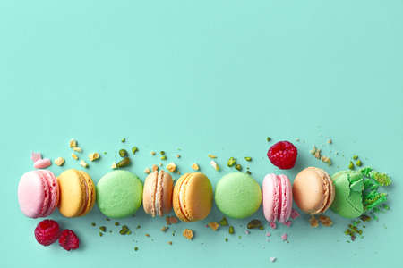 Row of colorful french macarons on blue background. Top view. Pastel colors Imagens