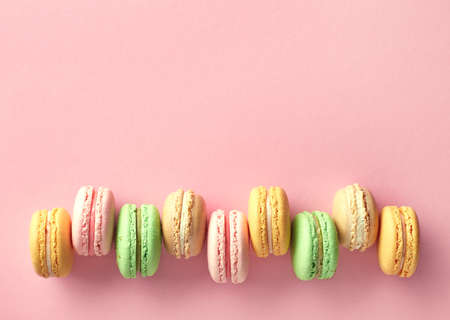 Row of colorful french macarons on pink background. Top view. Pastel colors 免版税图像