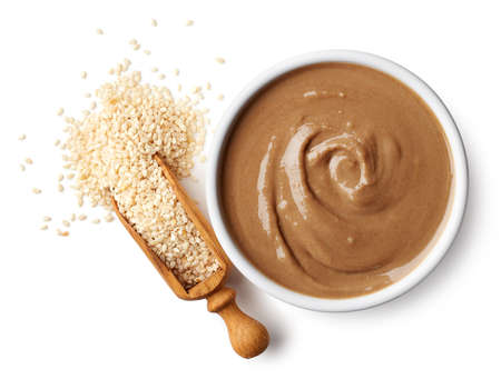 Bowl of tahini sauce and sesame seeds isolated on white background. Top view
